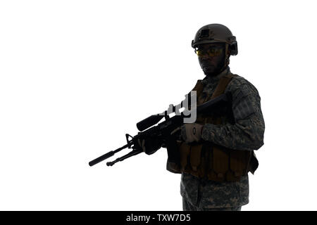 Silhouette of soldier wearing body armour and helmet holding modern weapon in hands and keeping position for fight. Confident male from American army with best weapon. White studio background. - Stock Photo