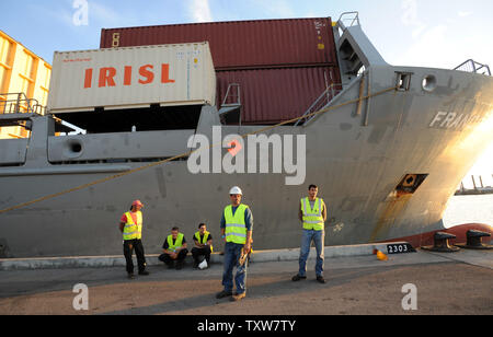 Israeli port workers stand beside the Antiqua-flagged Francop vessel at the Ashdod Port on November 4, 2009. The ship was seized by Israeli commandos in the Mediterranean Sea carrying hundreds of tons of Iranian supplied arms bound for Syria. UPI/Debbie Hill - Stock Photo