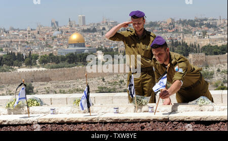 An Israeli soldier salutes while a comrade  places flowers and an Israeli flag on the grave of fallen soldiers at the military cemetery on the Mt. of Olives on the Eve of Memorial Day in Jerusalem, April 18, 2010.  Israeli will start the commemoration of 22,682 fallen soldiers and victims of terror attacks tonight when a siren will wail across the country to announce the start of Memorial Day.  UPI/Debbie Hill - Stock Photo
