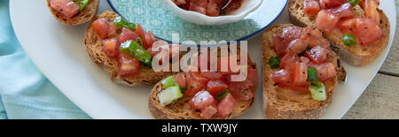 Close up view of tasty tomato Italian appetizers -  bruschetta, on slices of toasted baguette - Stock Photo