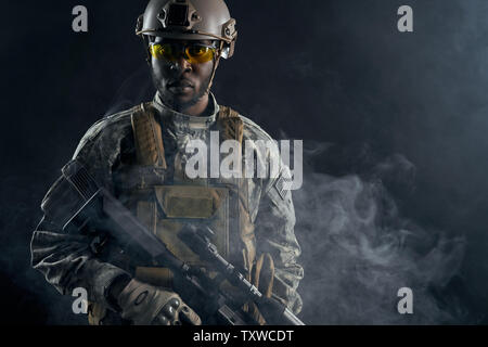 African ranker holding shotgun in hands, keeping position, after shooting. American soldier in glasses and helmet looking at camera. Concept of action of war operation. - Stock Photo