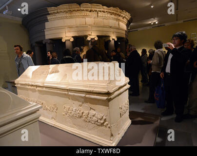 Visitors look at a sarcophagus beside a reconstruction of the tomb of King Herod  that was built in Herodian fortress, south of Jerusalem, displayed in an exhibition titled 'Herod the Great: The King's Final Journey,'  in the Israel Museum, Jerusalem, Israel, February 12, 2013. The exhibition deals with 40 years of archeological excavations of the life and legacy of King Herod who is remembered as the greatest builder in human history. He is known for elaborate palaces, fortresses, such as Masada, and the reconstruction of the Temple in Jerusalem during the Roman era. Herod ruled for over 30 y - Stock Photo