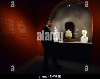 A visitor walks past statues of Cleopatra VII and Mark Anthony, which are part of an exhibition  titled 'Herod the Great: The King's Final Journey,'  in the Israel Museum, Jerusalem, Israel, February 12, 2013. The exhibition deals with 40 years of archeological excavations of the life and legacy of King Herod who is remembered as the greatest builder in human history. He is known for elaborate palaces, fortresses, such as Masada, and the reconstruction of the Temple in Jerusalem during the Roman era. Herod ruled for over 30 years in what is now known as the West Bank and Israel. He was respons - Stock Photo