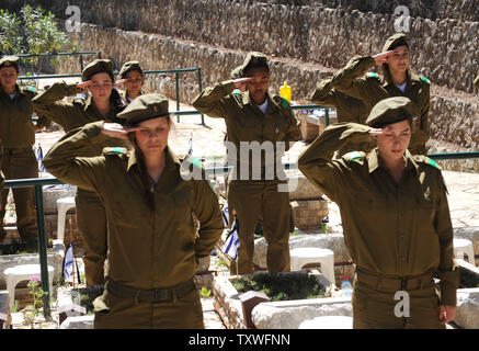 Israeli soldiers salute after decorating graves of fallen soldiers with national flags with black ribbons for Remembrance Day at the Mt. Herzl Military Cemetery in Jerusalem, Israel, April 14, 2013. Israel's Remembrance Day for fallen soldiers begins at sunset with a one minute siren.  UPI/Debbie Hill - Stock Photo