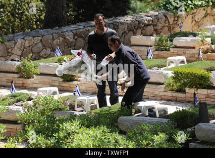 An Israeli places flowers on the grave of a fallen soldier for Remembrance Day at the Mt. Herzl Military Cemetery in Jerusalem, Israel, April 14, 2013. Israel's Remembrance Day for fallen soldiers begins at sunset with a one minute siren.  UPI/Debbie Hill - Stock Photo