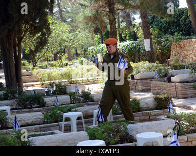 An Israeli soldier carries memorial candles and national flags with black ribbons to  decorate the graves of fallen soldiers  for Remembrance Day at the Mt. Herzl Military Cemetery in Jerusalem, Israel, April 14, 2013. Israel's Remembrance Day for fallen soldiers begins at sunset with a one minute siren.  UPI/Debbie Hill - Stock Photo