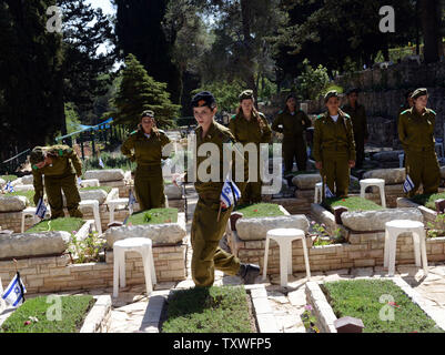 Israeli soldiers decorate the graves of fallen soldiers with national flags with black ribbons for Remembrance Day at the Mt. Herzl Military Cemetery in Jerusalem, Israel, April 14, 2013. Israel's Remembrance Day for fallen soldiers begins at sunset with a one minute siren.  UPI/Debbie Hill - Stock Photo