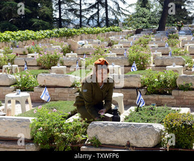 An Israeli soldier decorates the graves of fallen soldiers with national flags with black ribbons for Remembrance Day at the Mt. Herzl Military Cemetery in Jerusalem, Israel, April 14, 2013. Israel's Remembrance Day for fallen soldiers begins at sunset with a one minute siren.  UPI/Debbie Hill - Stock Photo