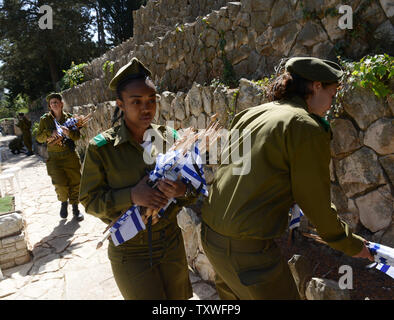 An Israeli soldier carries national flags with black ribbons to decorate the graves of fallen soldiers  for Remembrance Day at the Mt. Herzl Military Cemetery in Jerusalem, Israel, April 14, 2013. Israel's Remembrance Day for fallen soldiers begins at sunset with a one minute siren.  UPI/Debbie Hill - Stock Photo