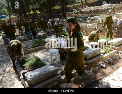 An Israeli soldier carries a national flags with black ribbons to  decorate the graves of fallen soldiers  for Remembrance Day at the Mt. Herzl Military Cemetery in Jerusalem, Israel, April 14, 2013. Israel's Remembrance Day for fallen soldiers begins at sunset with a one minute siren.  UPI/Debbie Hill - Stock Photo