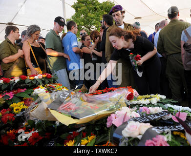 Lihi Greenberg, places flowers on the grave of her father, Major Amotz Greenberg, 45, after a military funeral in the cemetery in Hod HaSharon, Israel, July 20, 2014. Greenberg, a reserve soldier, was killed in a fight with Palestinian militants in Gaza on Saturday.  Eighteen Israeli soldiers and more than 350 Palestinians have lost their lives in the battle between Israeli forces and Hamas in Gaza.  UPI/Debbie Hill - Stock Photo