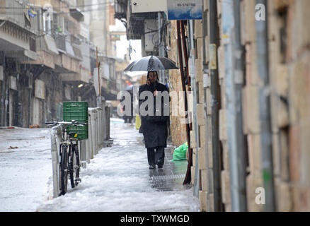 An Ultra-Orthodox Jew talks on a cellphone while walking in the snow and rain during a winter storm in Jerusalem, Israel, January 8, 2015.  A heavy winter storm is hitting the Middle East, while only 5 cm. or 1 inch of snow fell in Jerusalem. UPI/Debbie Hill - Stock Photo