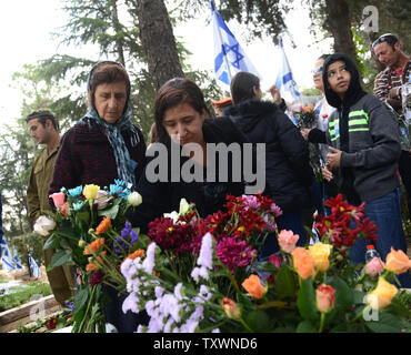 An Israeli woman places flowers on the grave of a family member, a fallen soldier, on Memorial Day in the Mt. Herzl Military Cemetery in Jerusalem, Israel, April 22, 2015. Thousands of Israelis visited cemeteries throughout the country to mourn the 23,320 fallen in Israel's battles since 1948. Photo by Debbie Hill/UPI - Stock Photo