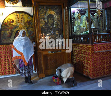 An Ethiopian woman kneels and prays in front of a Madonna and Child icon in the Church of Nativity, where tradition believes Jesus Christ was born, in Bethlehem, West Bank, December 20, 2015. Photo by Debbie Hill/ UPI - Stock Photo