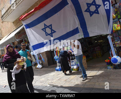 A Palestinian woman carries a baby past a store selling Israeli national flags for Israel's  Memorial Day for fallen soldiers and terror victims and Independence Day in Jerusalem, Israel , May 10, 2016. An one-minute siren will sound Tuesday night to begin Israel's Memorial Day for fallen soldiers and civilian terror victims. Israel will commemorate 23,447 IDF soldiers and terror victims killed since 1860. Official ceremonies will be held at military cemeteries throughout Israel on Wednesday morning and the country's mourning will turn to festivities when Israel's 68th Independence Day begins - Stock Photo