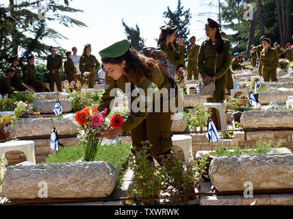 An Israeli soldier places flowers on a grave on Israel's  Memorial Day for fallen soldiers and terror victims in the Mount Herzl Military Cemetery in Jerusalem, Israel May 11, 2016.  Israel is marking Memorial Day to commemorate 23,477 fallen soldiers and 2,517 civilians killed in terror  attacks hours before the country's mourning turns to festivities when Israel's 68th Independence Day begins Wednesday night. Photo by Debbie Hill/UPI - Stock Photo