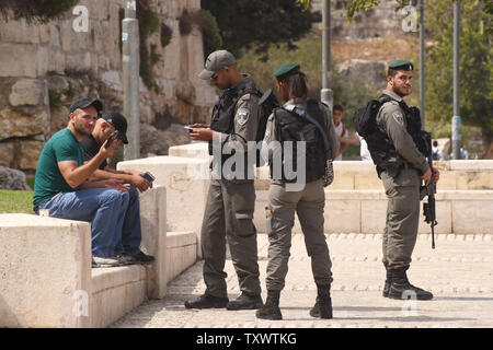 Israeli border police check the identity card of a Palestinian outside the Old City in East Jerusalem, September 22, 2016. Israeli soldiers arrested 23 Palestinians early Thursday in raids in several East Jerusalem neighborhoods in a search for arms and suspected offenders in the new wave of stabbing terror attacks.  The Israeli Defense establishment expects a rise of attacks ahead of the upcoming Jewish High Holy Days in early October.  Photo by Debbie Hill/ UPI - Stock Photo