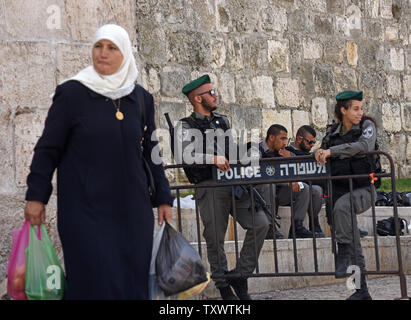 A Palestinian passes Israeli border police on guard outside the Old City in East Jerusalem, September 22, 2016. Israeli soldiers arrested 23 Palestinians early Thursday in raids in several East Jerusalem neighborhoods in a search for arms and suspected offenders in the new wave of stabbing terror attacks.  The Israeli Defense establishment expects a rise of attacks ahead of the upcoming Jewish High Holy Days in early October.  Photo by Debbie Hill/ UPI - Stock Photo