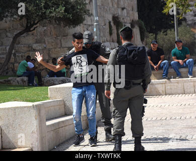 Israeli border police search a Palestinian youth outside the Old City in East Jerusalem, September 22, 2016. Israeli soldiers arrested 23 Palestinians early Thursday in raids in several East Jerusalem neighborhoods in a search for arms and suspected offenders in the new wave of stabbing terror attacks.  The Israeli Defense establishment expects a rise of attacks ahead of the upcoming Jewish High Holy Days in early October.  Photo by Debbie Hill/ UPI - Stock Photo