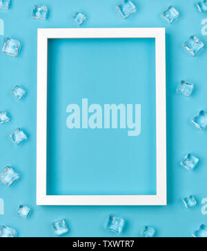 Flat lay mockup with white frame and ice cubes on blue background. - Stock Photo