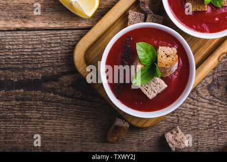 Traditional tomato soup garnished with rye bread croutons and thyme, plant based food, close up, selective focus, top view - Stock Photo