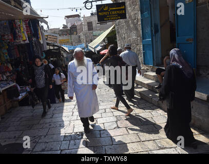 An Ultra-Orthodox Jew wears a white robe as he walks past a Muslim woman in the Old City of Jerusalem, on Rosh HaShanah, the Jewish New Year, and the Islamic New Year, September 21, 2017. Both religions follow the lunar calendar. Photo by Debbie Hill/UPI - Stock Photo