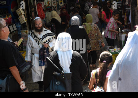 An Ultra-Orthodox Jew wears and white robe and prayer shawl while walking between Muslim women in the Old City of Jerusalem, on Rosh HaShanah, the Jewish New Year, and the Islamic New Year, September 21, 2017. Both religions follow the lunar calendar. Photo by Debbie Hill/UPI - Stock Photo