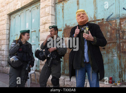 Israeli border police stand beside a settler wearing a mask of U.S. President Donald Trump during the Jewish festival Purim parade in Hebron, West Bank, March 1, 2018. Purim commemorates the saving of the Jewish people from Haman in the ancient Persian Empire as told in the book of Esther. Photo by Debbie Hill/UPI - Stock Photo