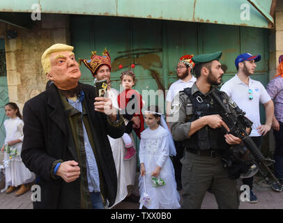 An Israeli border police stands beside a settler wearing a mask of U.S. President Donald Trump during the Jewish festival Purim parade in Hebron, West Bank, March 1, 2018. Purim commemorates the saving of the Jewish people from Haman in the ancient Persian Empire as told in the book of Esther. Photo by Debbie Hill/UPI - Stock Photo