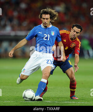 Andrea Pirlo (L) of Italy is challenged by Xavi of Spain during the Euro 2012 Final match at the Olympic Stadium in Kiev, Ukraine on July 1, 2012. UPI/Chris Brunskill - Stock Photo