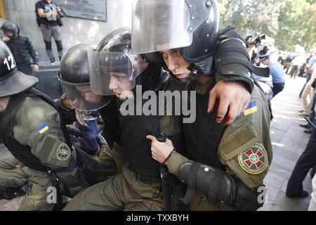 Ukrainian riot police officer is injured after a grenade blast during a clash with protesters outside the parliament in Kiev on August 31, 2015. Hundreds of people gathered in front of the parliament to protest against an approved  constitutional amendment on decentralization to separatist regions.   Photo by Ivan Vakolenko/UPI - Stock Photo