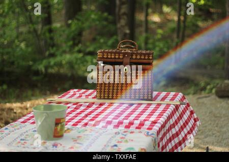 A brown woven bag and a mug on a red checkered cloth in a forest - Stock Photo