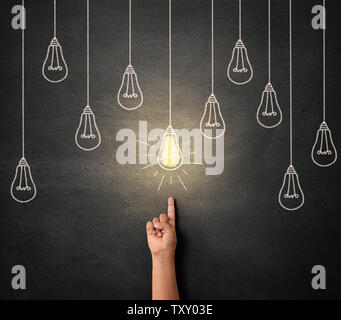 Child hand pointing at the glowing light bulb drawn on the concrete wall - Stock Photo