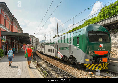 COMO, ITALY - JUNE 2019: Two people walking on the platform in the town centre station of North Lake Como, A modern electric train is at a platform