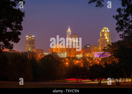 Skyline of Raleigh, North Carolina at dusk with the roadway in the foreground. - Stock Photo