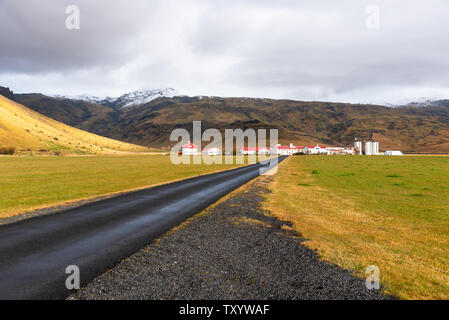 Empty paved road to a farm at the foot of mountain in Iceland on a cloudy autumn day - Stock Photo