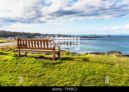 Empty wooden bench in a park overlooking the coastal town of North Berwick on a sunny autumn day. Scotland, UK - Stock Photo