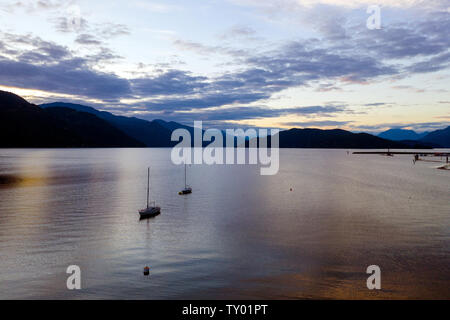 Aerial, or elevated view of two old and battered white sailboats with wind-board down, and single wiggling on a softly waving on a lake at sunset in B - Stock Photo