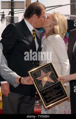 British actor Sir Roger Moore (L) and his wife, actress Christina Tholstrup kiss during an unveiling ceremony honoring him with the 2,350th star on the Hollywood Walk of Fame in Los Angeles on October 11, 2007. Moore appeared in 1973 in his first James Bond film 'Live and Let Die.' He also starred as Simon Templar in the TV series 'The Saint.'  (UPI Photo/Jim Ruymen) - Stock Photo