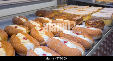 Cream cakes for sale in retail display cabinet - Stock Photo