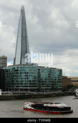 London on a grey day seen from Tower Bridge over the Thames and the tall modern glass buildings City Hall and The Shard with their contrasting shapes - Stock Photo