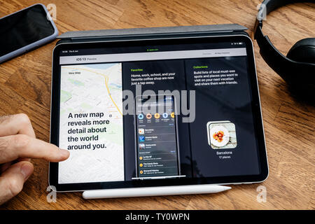 Paris, France - Jun 6, 2019: Man reading on Apple iPad Pro tablet about latest announcement of at Apple Worldwide Developers Conference (WWDC) - showing the IOS 13 preview with maps app - Stock Photo