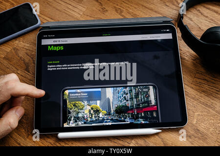 Paris, France - Jun 6, 2019: Man reading on Apple iPad Pro tablet about latest announcement of at Apple Worldwide Developers Conference (WWDC) - showing the new Maps with 3d experience - Stock Photo