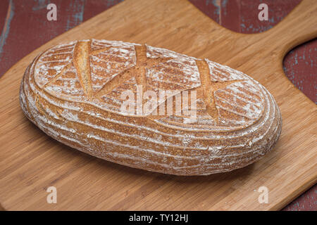 Loaf of sourdough bread on wooden board - Stock Photo