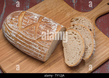 Loaf of sourdough bread with slices on wooden board - Stock Photo