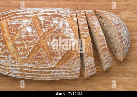 Loaf of sourdough bread sliced on wooden board - Stock Photo