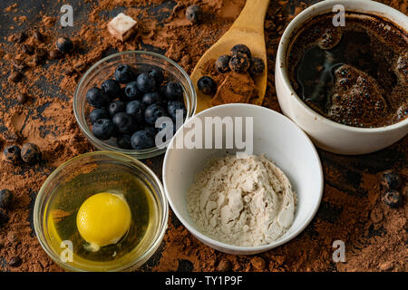 top view of ingredients for cooking or baking chocolate on the table, blueberry, egg, flour, cocoa and chocolates - Stock Photo