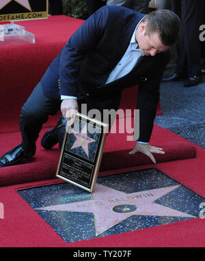 Actor Alec Baldwin holds a replica plaques as takes a gander of his star during an unveiling ceremony honoring him with the 2,433rd star on the Hollywood Walk of Fame in Los Angeles on February 14, 2011.  UPI/Jim Ruymen - Stock Photo