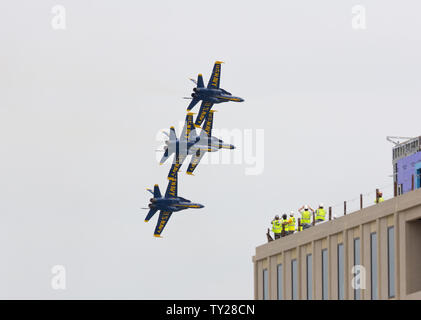 Annapolis, Maryland, USA. 22nd May, 2019. The Blue Angels, the U.S. Navy's flight demonstration squadron, fly Boeing F/A-18 Hornet aircraft numbers one, two, three, and four (1,2,3, and 4) during an air show as part of Commissioning Week 2019 at the United States Naval Academy (USNA); as construction workers watch and film atop partially finished Hopper Hall, to be the first academic building named after a woman at a major service academy in the U.S. Kay Howell/Alamy - Stock Photo