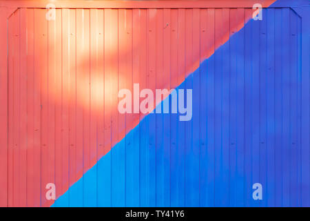 Background made of metal profile painted in blue and red on the fence or container backlit by the sun - Stock Photo